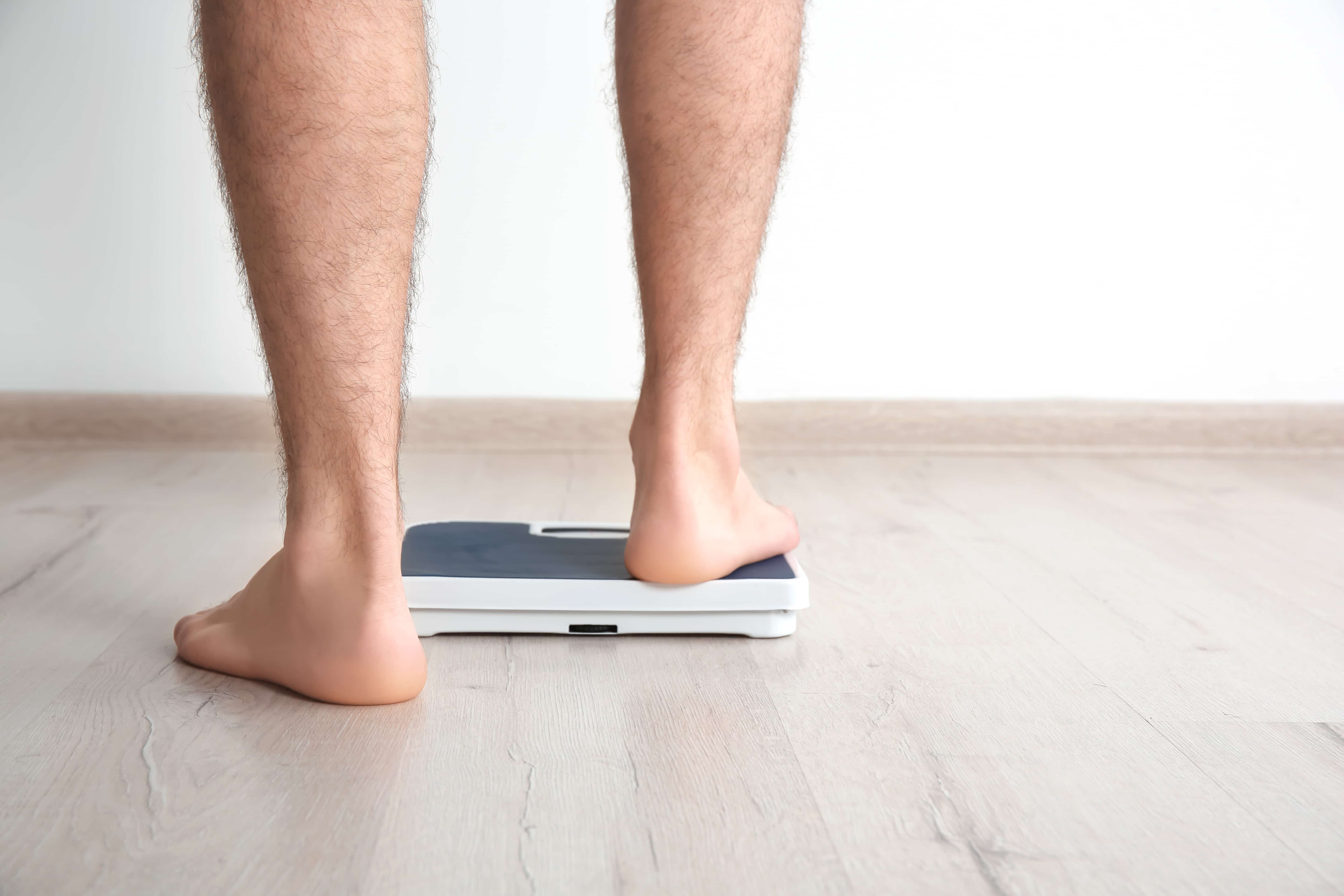 man stepping on scales